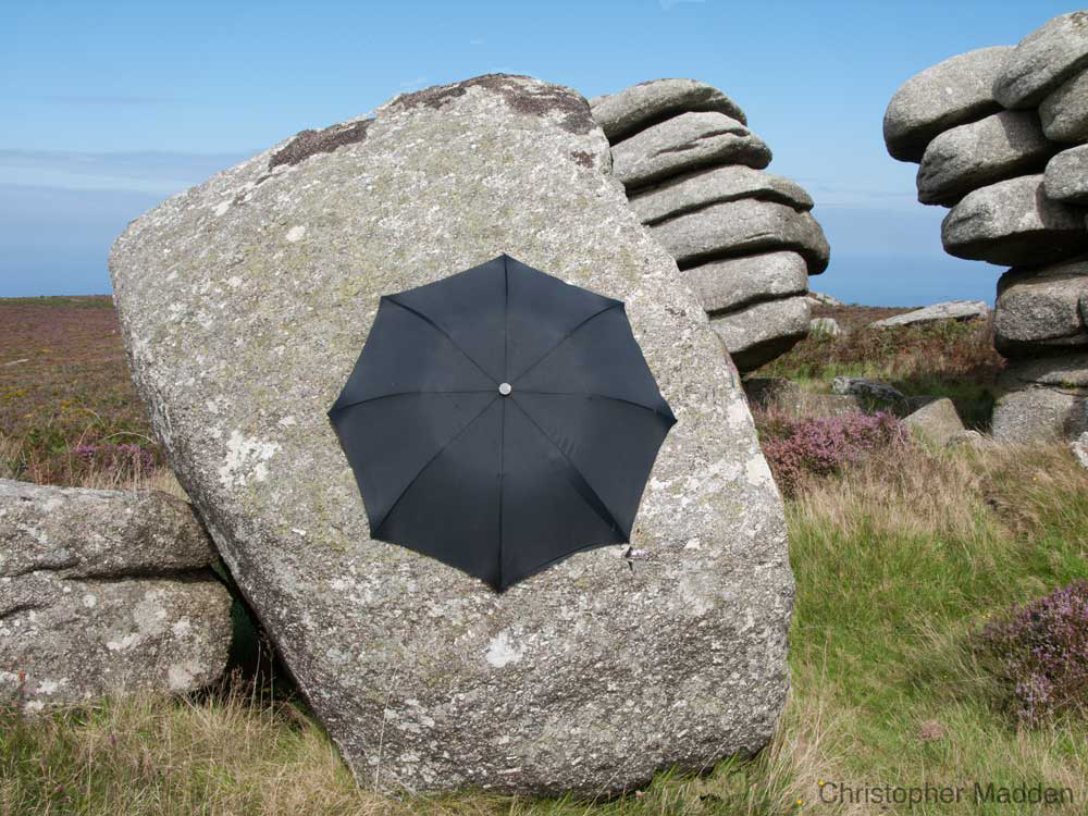 contemporary art in the environment - umbrella clinging like a limpet to a rock, Cornwall
