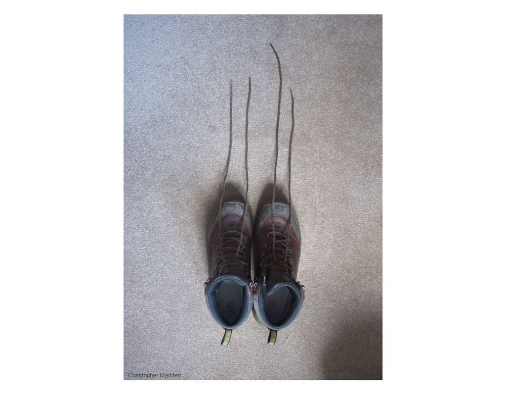 contemporary photography - shoes with their laces extended - slightly sinister