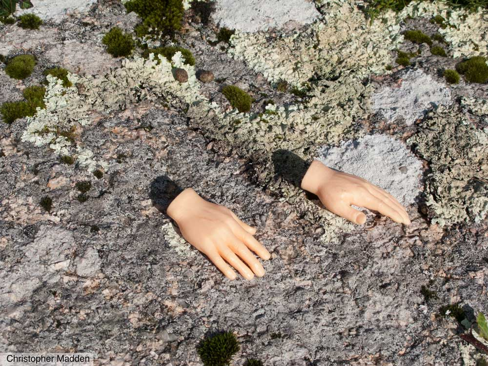 Contemporary art - disembodied toy hands on a rock near St Ives