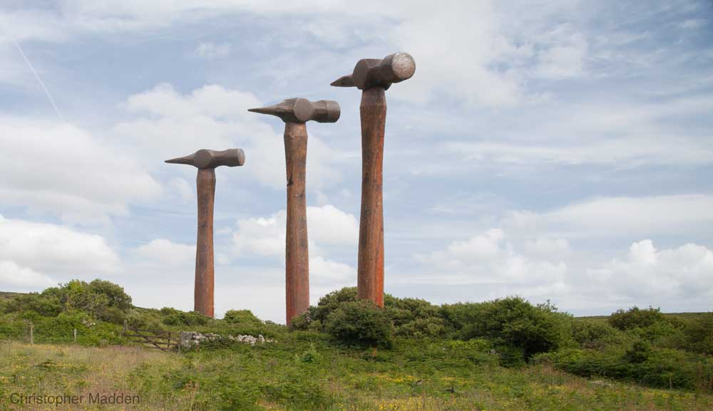 contemporary sculpture  in the landscape - oversized hammers