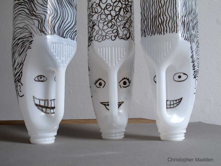 contemporary environmental art sculpture created from consumer waste - heads created from plastic milk bottles