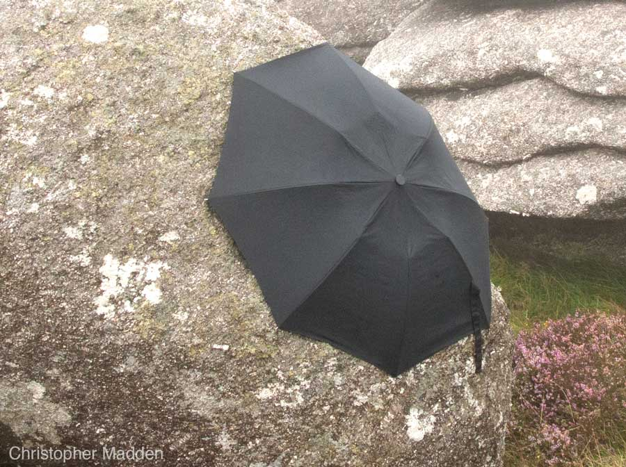 contemporary land art - umbrella clinging to a rock, Cornwall